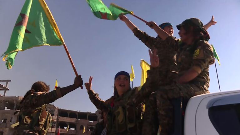 Members of the women's brigades of the Kurdish YPJ celebrate the victory over Islamic State