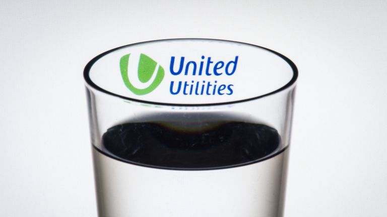 The logo of water company United Utilities seen through a glass of water