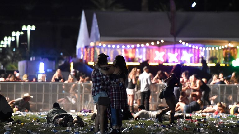 Festival-goers hold each other after the deadliest mass shooting in US history