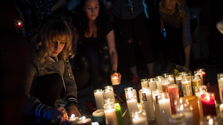 Mourners light candles during a vigil for victims