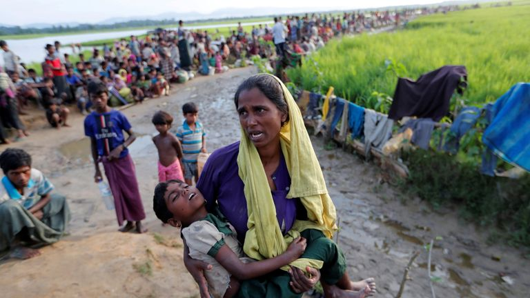 A Rohingya refugee who crossed the border from Myanmar a day before, carries her daughter and searches for help in Palang Khali, Bangladesh