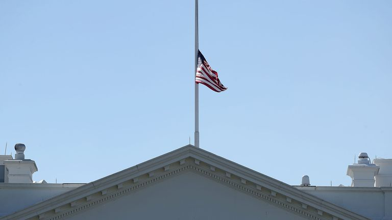 The US flag flies at half mast above the White House