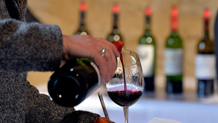 Wine being poured into a glass at a tasting in Saint-Emilion, France