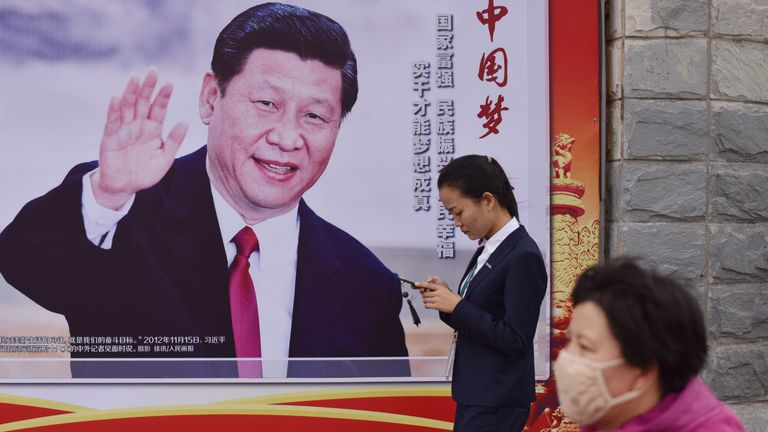 People walk past a poster featuring Chinese President Xi Jinping with a slogan reading 'Chinese Dream, People's Dream' beside a road in Beijing on October 16, 2017