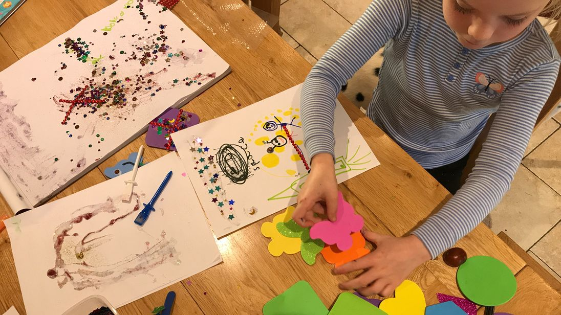 A child works on a colourful art project