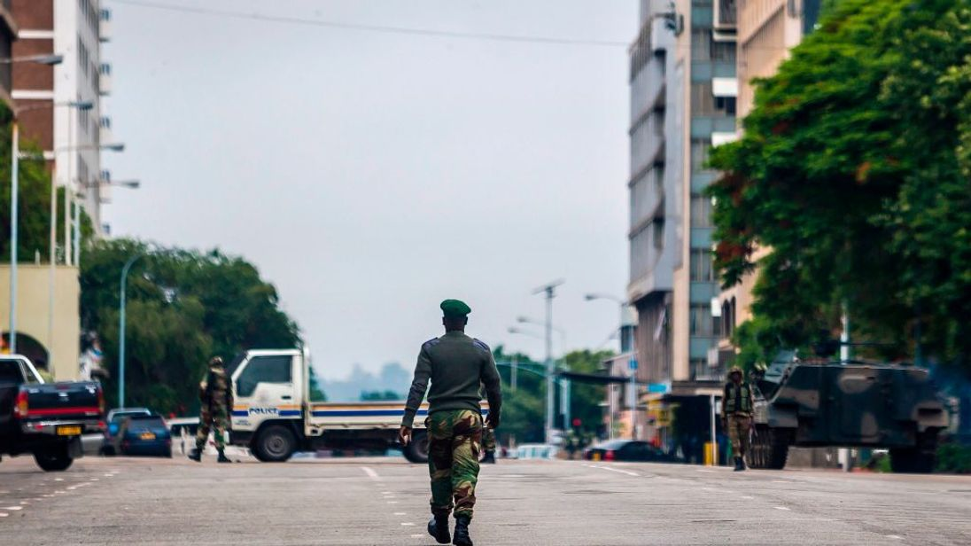 A soldier walks down a deserted main road in central Harare