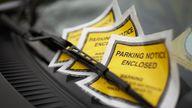 Parking tickets under windshield wiper, close-up