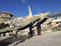 People walk past a damaged building following an earthquake in Darbandikhan in Sulaimaniya Governorate, Iraq