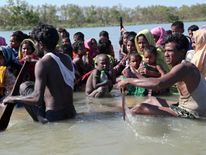 Rohingya refugees cross the Naf river on an improvised raft