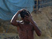 A Rohingya refugee takes a bath in Thankhali refugee camp
