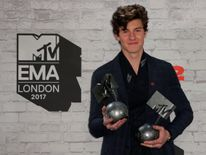 Canadian singer-songwriter Shawn Mendes poses with two of his three awards for best song for 'There's Nothing Holdin' Me Back', best artist and biggest fans i