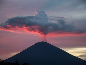 A general view shows Mount Agung from Amed beach in Karangasem on Indonesia's resort island of Bali on November 30, 2017. Thousands of foreign tourists were expected to leave Bali by plane on November 30 following a nearly three-day airport shutdown sparked by a rumbling volcano on the Indonesian holiday island