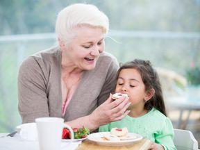 A grandmother feeds a biscuit to her granddaughter. File pic