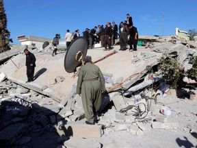Residents look at a damaged building following an earthquake in the town of Darbandikhan, near the city of Sulaimaniyah, Iraq