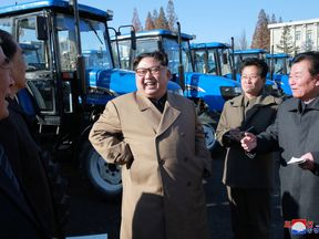 North Korean leader Kim Jong Un laughed with tractor factory bosses in his first public outing in two months