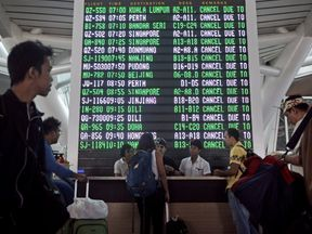 Passengers ask staff about their flights near the flight screen after Ngurah Rai airport closed their operation due to eruption of Mount Agung