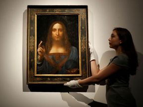 """RTX3HXYK24 Oct. 2017London, United KingdomMembers of Christie's staff pose for pictures next to Leonardo da Vinci's """"Salvator Mundi"""" painting which will be auctioned by Christie's in New York in November, in London, Britain October 24, 2017. REUTERS/Peter Nicholls NO RESALES. NO ARCHIVES"""