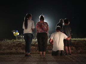 People pray at a field on the edge of town where 26 crosses were placed to honor the 26 victims killed at the First Baptist Church of Sutherland Springs on November 6, 2017 in Sutherland Springs, Texas