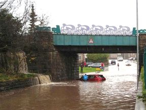 A car is stuck in floodwater underneath a railway bridge in Cumbria