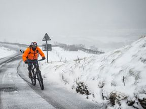 A cyclist on the Buttertubs Pass in the Yorkshire Dales as snow hits the UK in February 2017