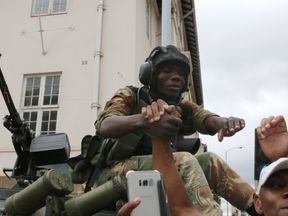 A soldier shakes hands with protesters calling for Mugabe to step down