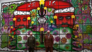 Gilbert and George stand in front of one of their pieces