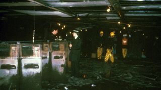 Police and fire officers in the fire-damaged ticket hall at King's Cross Underground Station, scene of a blaze in which more than 30 people perished.