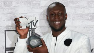 BRITAIN-ENTERTAINMENT-MUSIC-MTV-EMA-AWARDS-WINNERS British grime and hip hop artist Stormzy poses in the winners' area with his worldwide act award during the 2017 MTV Europe Music Awards (EMA) at Wembley Arena in London on November 12, 2017. / AFP PHOTO / Daniel LEAL-OLIVAS (Photo credit should read DANIEL LEsAL-OLIVAS/AFP/Getty Images)