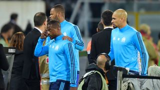 Patrice Evra (C) is escorted off the pitch by teammates after kicking one of his team's supporters before a Europa League game