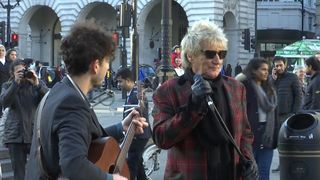 Rod Stewart gives an impromptu performance with a busker in London's Piccadilly Circus