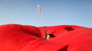 A Houthi follower emerges from a gap in a flag as he attends a rally to show support to the Palestinians in Sanaa, Yemen
