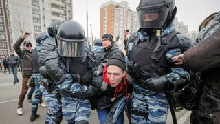 Police officers detain a participant of a Russian nationalist march on National Unity Day in Moscow, Russia