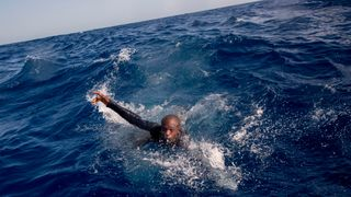 A migrant tries to board a boat of the German NGO Sea-Watch in the Mediterranean Sea