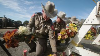 Police move flowers placed at a barricade near the First Baptist Church of Sutherland Springs, Texas