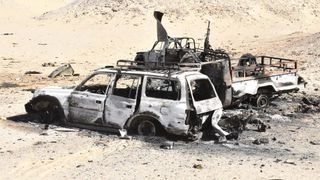 Destroyed Egyptian police vehicles which came under fire from a heavily armed militant group, lie in the desert at the Bahariya Oasis in, southwest of Cairo
