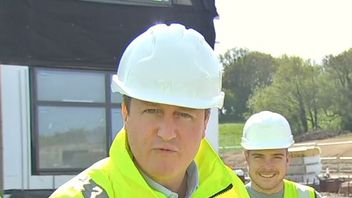 David Cameron addresses the media at a construction site.