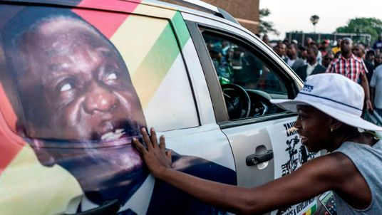 A supporter of Emmerson Dambudzo Mnangagwa touches an image of the politician glued on a SUV at the ZANU-PF headquarter in Harare, on November 22, 2017