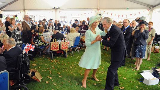 The Duchess of Cornwall dances with Royal Navy Veteran Jim Booth during the 70th Anniversary commemorations of VJ Day (Victory over Japan) at the Royal British Legion reception in the College Gardens of Westminster Abbey on August 2015.