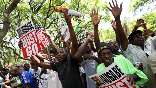 Protesters call for Zimbabwean President Robert Mugabe to resign across the road from parliament in Harare