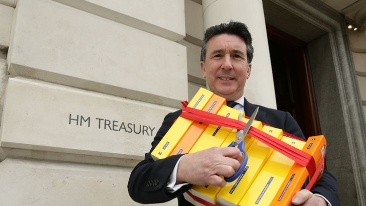 ICAS Chief Executive Anton Colella holding the books which comprise the UK tax code - which contain and up to 20,000 pages - outside the Treasury, in London, to call for simplification of the UK Tax Code. PRESS ASSOCIATION Photo. Picture date: Wednesday March 25, 2015. Photo credit should read: Yui Mok/PA Wire