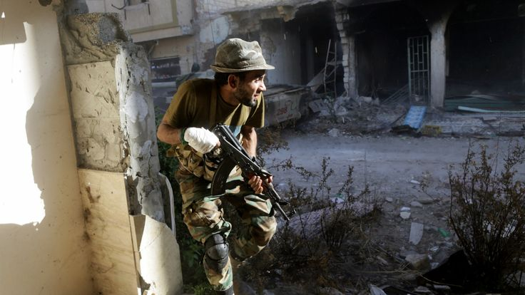 A member of the Libyan National Army takes cover during clashes with the Islamist militants. Continue through for more pictures