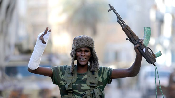 A member of the Libyan National Army gestures as he holds his weapon during clashes with Islamist militants