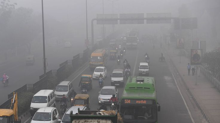 Commuters travel amid the smog in New Delhi