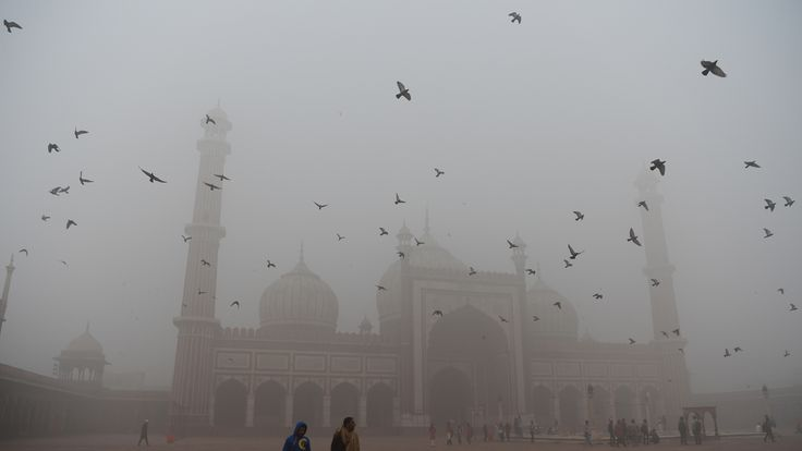 Visitors walk through the courtyard of Delhi's Jama Masjid in the smog