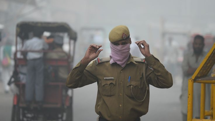 An Indian policeman covers his face with handkerchief as he walks in the smog