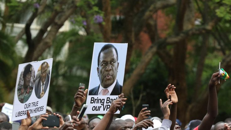 Protesters hold posters showing support for Emmerson Mnangagwa