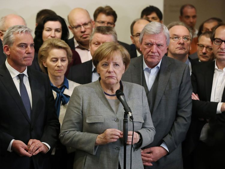 Angela Merkel stands with members of her party to address the media after the talks collapse