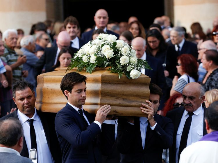 The journalists's sons, Matthew and Paul, carry their mother's coffin