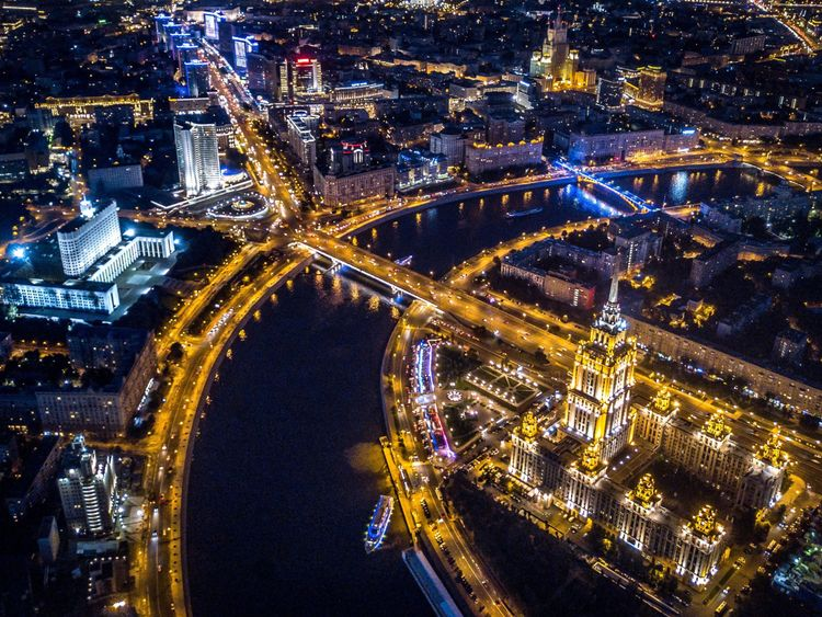 An aerial view taken with a drone on late August 12, 2017 shows the Radisson Royal Hotel (R) opposite the Russian government headquarters (L) as boats pass on the Moskva River in Moscow