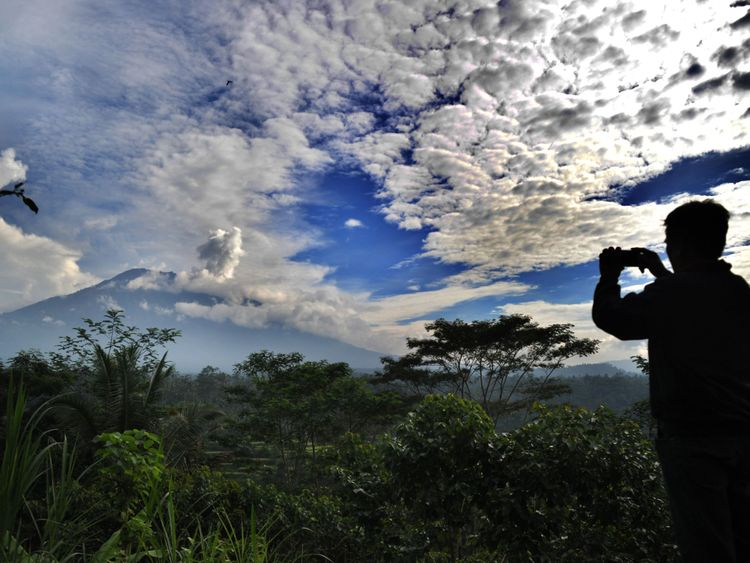 TOPSHOT - A man takes a photo as a puff of smoke comes from Mount Agung volcano, taken from the Rendang sub-district in Karangasem Regency on Indonesia's resort island of Bali on November 23, 2017. Thousands living in the shadow of the rumbling volcano on Indonesia's resort island of Bali fled on November 22 as fears grow that it could erupt for the first time in more than 50 years. / AFP PHOTO / SONNY TUMBELAKA (Photo credit should read SONNY TUMBELAKA/AFP/Getty Images)